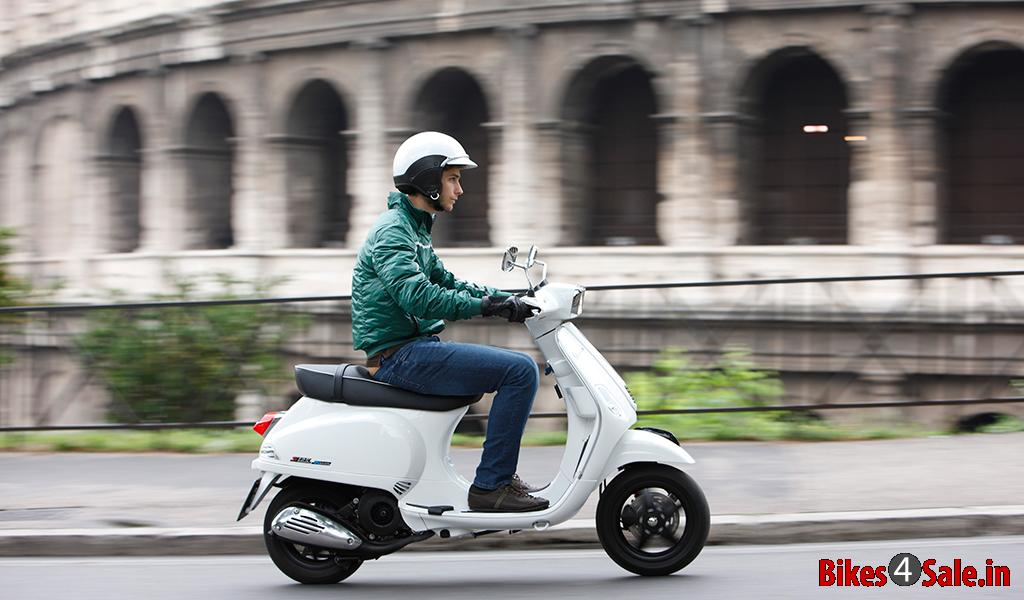 Picture Showing The Side View Of A Guy Riding The Vespa S